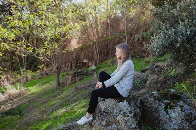 Giovane donna che si siede su una grande pietra