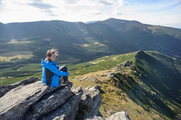 Giovane donna che si siede su una roccia in montagna