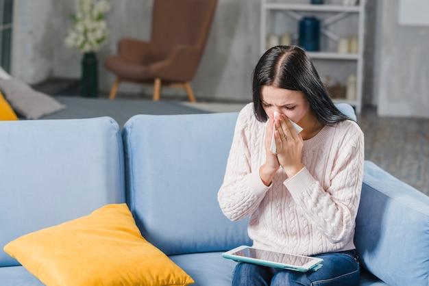 Giovane donna che si siede sul divano che soffia il naso guardando la tavoletta digitale