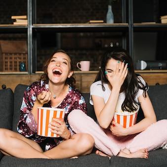 Giovane donna che si siede sul divano ridendo mentre si guarda film