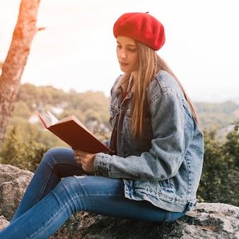 Giovane donna che si siede sul libro di lettura rock