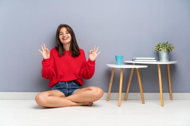 Giovane donna che si siede sul pavimento che mostra un segno giusto con le dita