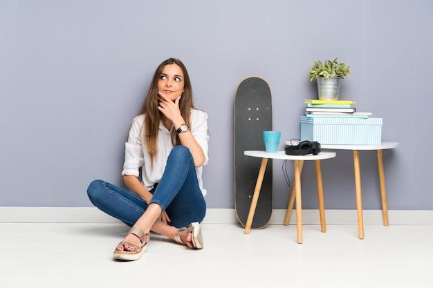 Giovane donna che si siede sul pavimento che pensa un'idea