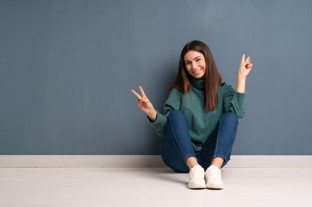 Giovane donna che si siede sul pavimento che sorride e che mostra il segno di vittoria con entrambe le mani