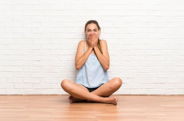 Giovane donna che si siede sul pavimento con espressione facciale sorpresa