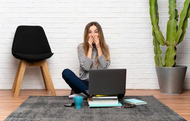 Giovane donna che si siede sul pavimento con il suo laptop con espressione facciale a sorpresa