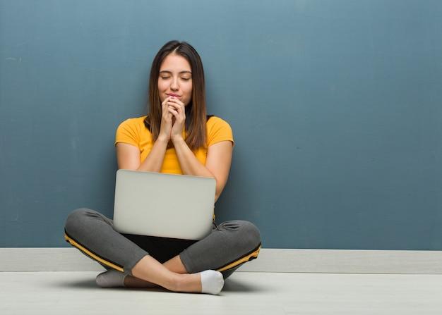 Giovane donna che si siede sul pavimento con un computer portatile che prega molto felice e fiducioso