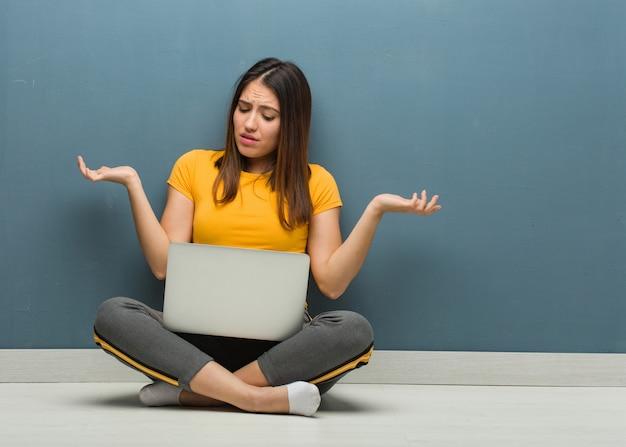 Giovane donna che si siede sul pavimento con un computer portatile confuso e dubbioso