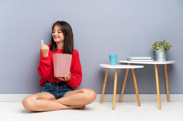 Giovane donna che si siede sul pavimento e che tiene i popcorn