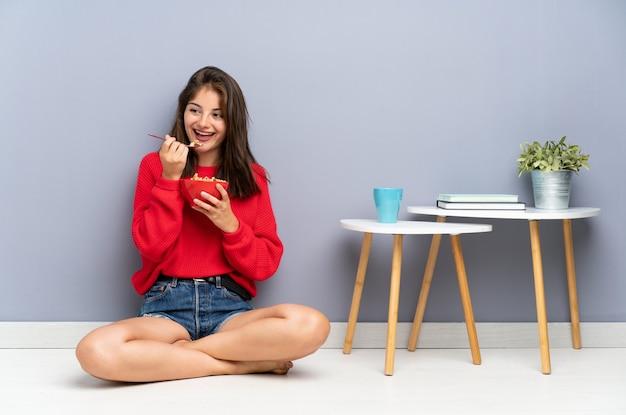 Giovane donna che si siede sul pavimento e che tiene una ciotola di cereali