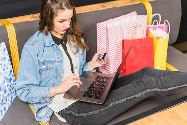 Giovane donna che si siede sul sofà che compera online con la carta di debito