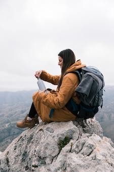 Giovane donna che si siede sulla cima della montagna con il suo zaino che tiene la bottiglia di acqua