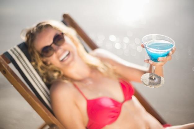 Giovane donna che si siede sulla poltrona con la bevanda del cocktail