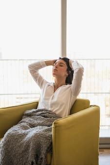 Giovane donna che si siede sulla poltrona rilassante in balcone