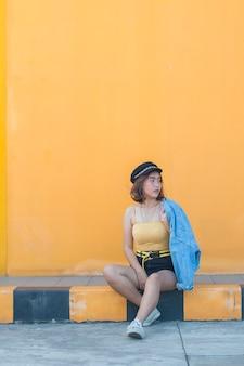 Giovane donna che si siede sulla strada con il muro di mattoni gialli