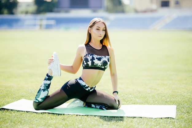 Giovane donna che si siede sulla stuoia di yoga verde chiaro che la allunga indietro, gambe e corpo