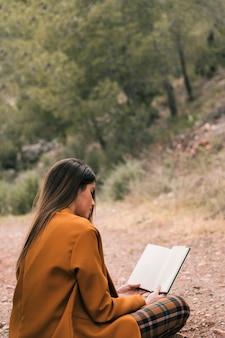 Giovane donna che si siede sulla terra leggendo il libro