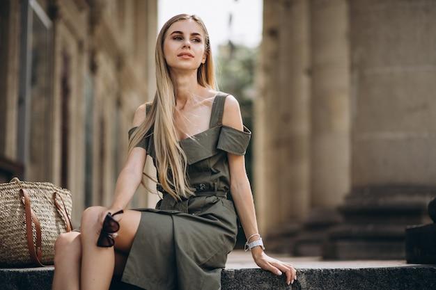 Giovane donna che si siede sulle scale di un vecchio bvuilding