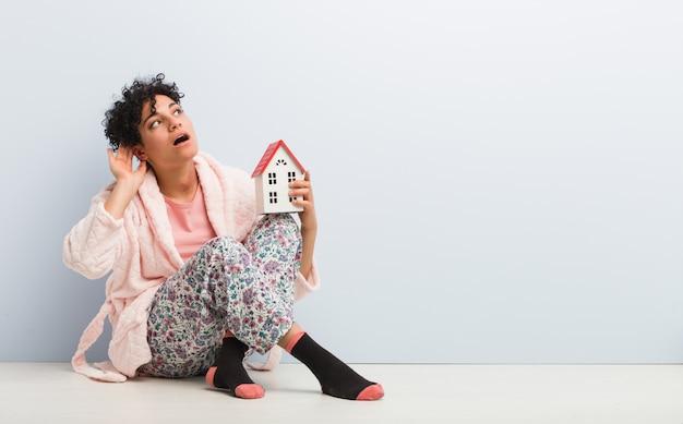 Giovane donna che si siede tenendo un'icona della casa