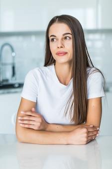 Giovane donna che si siede un tavolo in cucina.