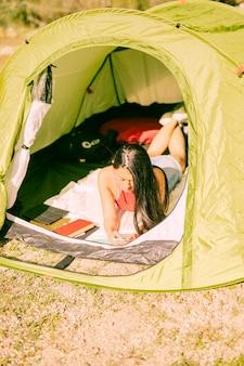 Giovane donna che si trova in tenda con lo smartphone