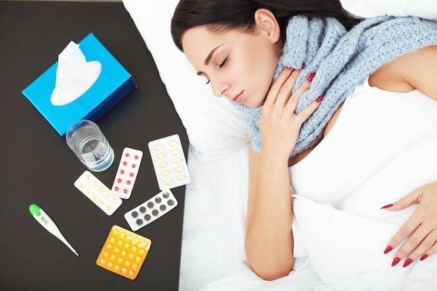 Giovane donna che si trova sul letto e che tiene le pillole della bolla della medicina