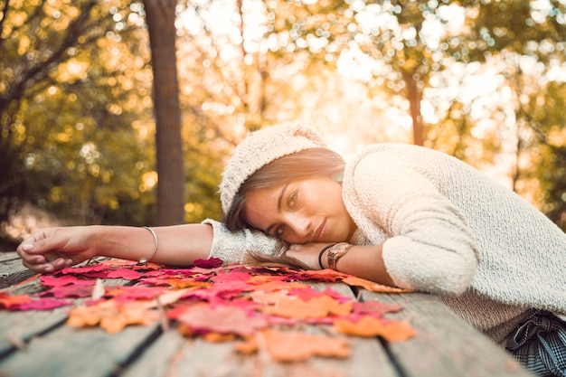 Giovane donna che si trova sul tavolo con foglie d'autunno