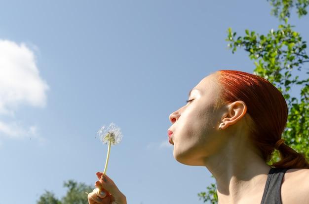 Giovane donna che soffia il dente di leone