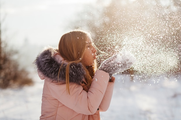 Giovane donna che soffia neve dalle mani