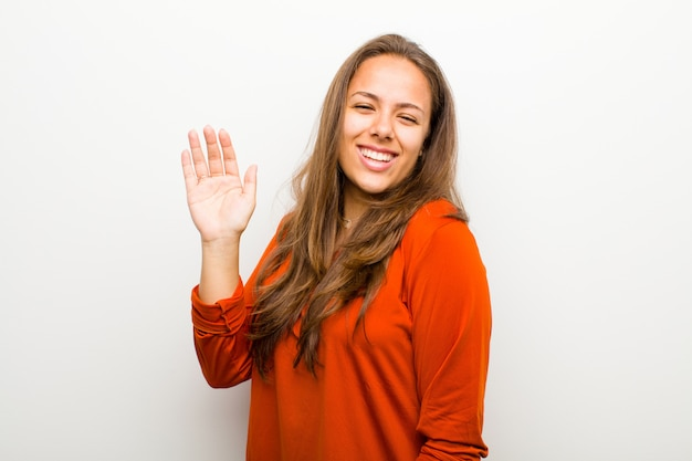 Giovane donna che sorride allegramente e allegramente, agitando la mano, dandovi il benvenuto e salutandovi, o salutandovi