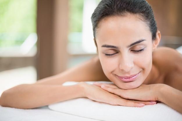 Giovane donna che sorride mentre rilassandosi sulla tavola di massaggio