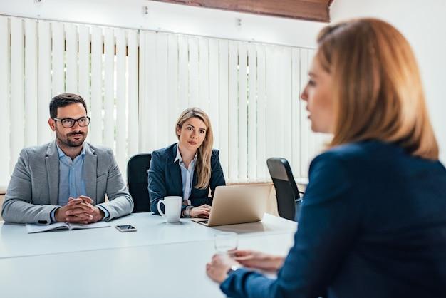 Giovane donna che spiega le idee ad un socio in affari alla riunione