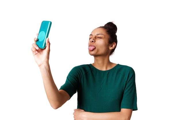 Giovane donna che sporge la lingua e prendendo selfie