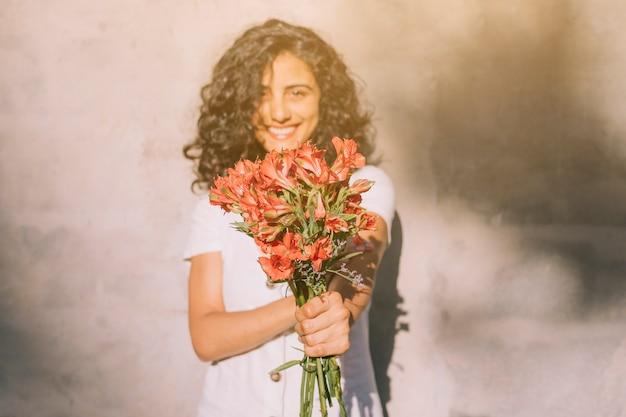 Giovane donna che sta contro il mazzo di rosso del fiore di alstroemeria della tenuta della parete in mani