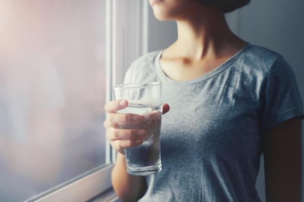 Giovane donna che sta e che tiene acqua di vetro vicino alla finestra. concetto sano