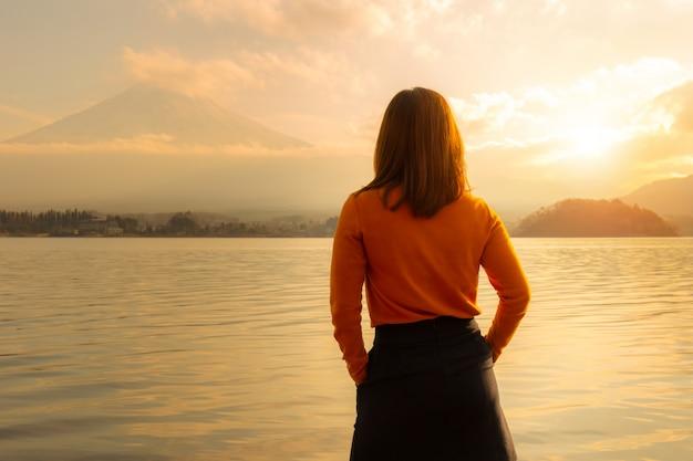 Giovane donna che sta indietro e che guarda fuji montagnoso dal lato di kawaguchi del lago nel paese del giappone