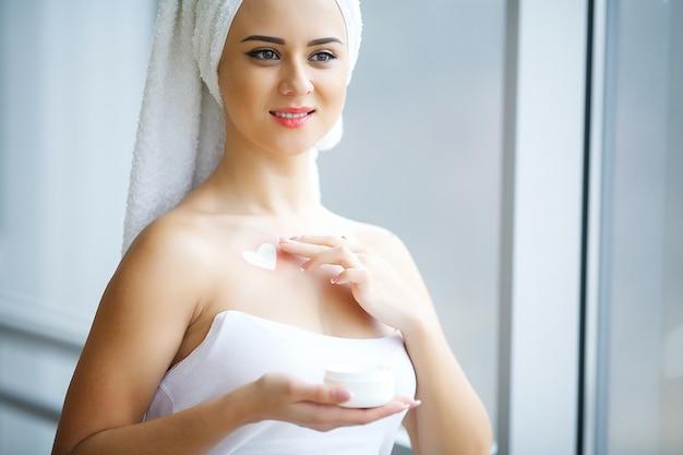 Giovane donna che sta nel bagno e che applica la crema di fronte di mattina