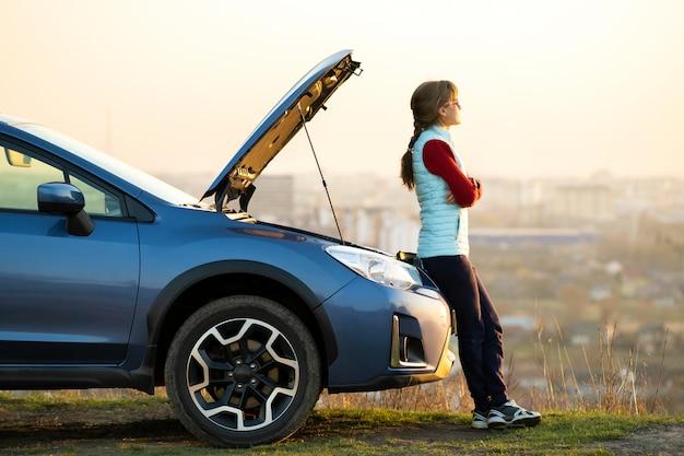 Giovane donna che sta vicino all'automobile ripartita con il cappuccio spuntato che ha problemi con il suo veicolo. driver femminile che aspetta aiuto accanto all'auto di disfunzione.