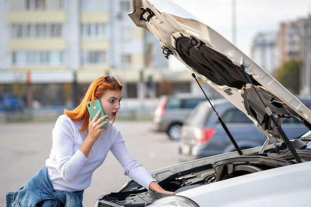 Giovane donna che sta vicino all'automobile rotta con il cappuccio schioccato che parla sul suo telefono cellulare mentre aspettando aiuto.