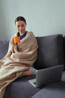 Giovane donna che stringe a sé in una coperta calda con un computer portatile e una tazza di tè