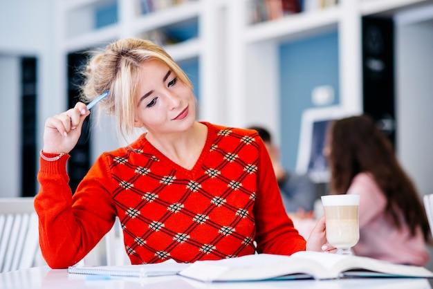 Giovane donna che studia allo scrittorio in biblioteca
