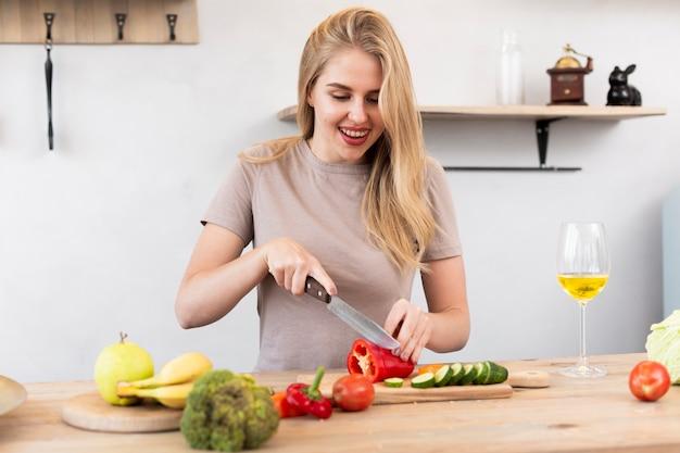 Giovane donna che taglia il peperone dolce in cucina