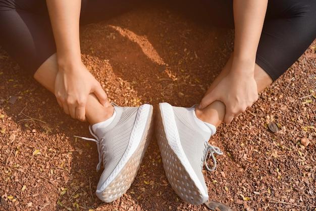 Giovane donna che tiene alla caviglia nel dolore sulla pista dello stadio. piede commovente della donna atletica dovuto distorsione.