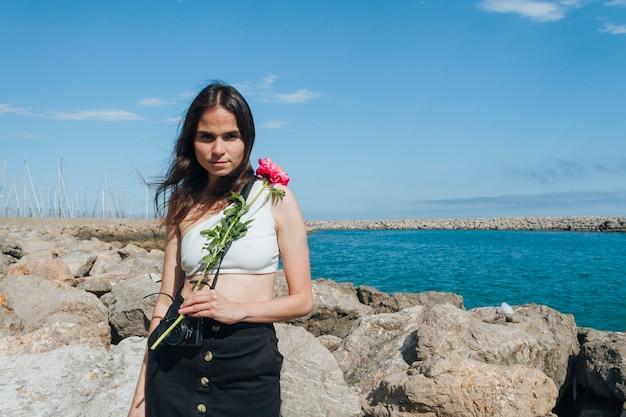 Giovane donna che tiene bello fiore e che esamina macchina fotografica che sta mare vicino
