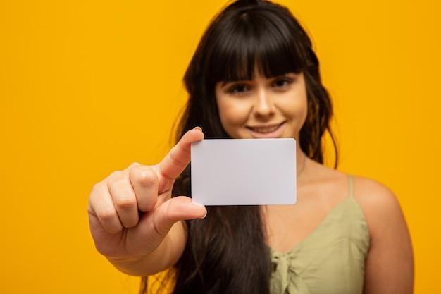 Giovane donna che tiene biglietto da visita bianco in bianco