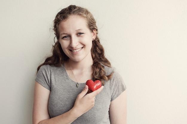 Giovane donna che tiene cuore rosso, assicurazione sanitaria, concetto di donazione