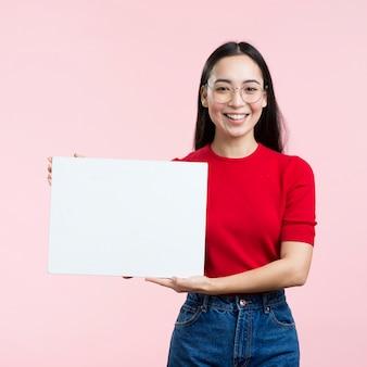 Giovane donna che tiene foglio di carta bianco