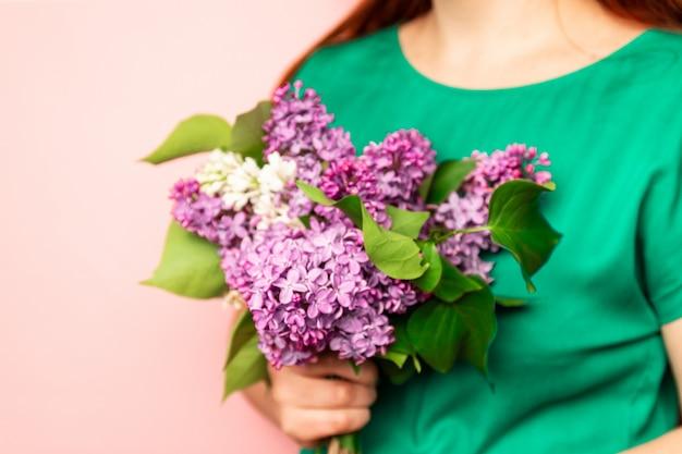 Giovane donna che tiene i fiori lilla