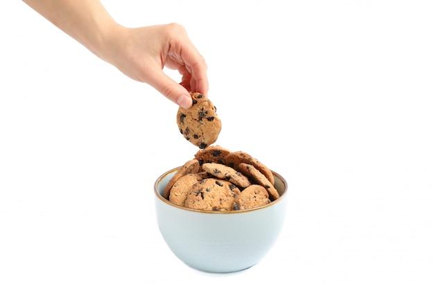 Giovane donna che tiene il biscotto di pepita di cioccolato saporito sopra la ciotola su fondo bianco, primo piano