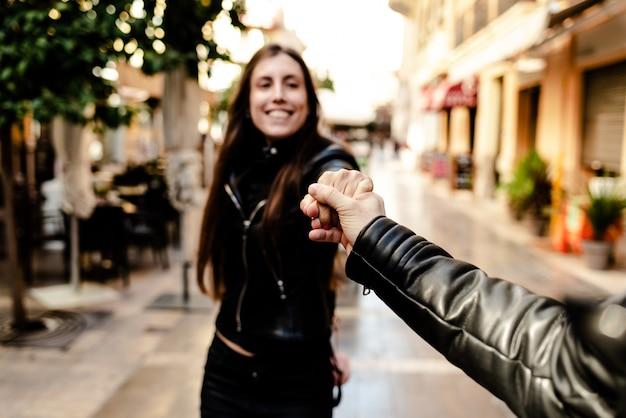 Giovane donna che tiene il braccio del suo ragazzo